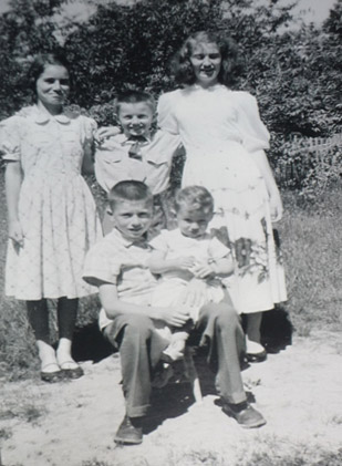 A picture of the five of us outside at the Quinn house.  I'm thinking this was taken on a Sunday, judging by the fact that I'm wearing my Sunday tie.  I've got my arms around my big sisters Marjorie and Katharine.  Johnny is sitting on a little stool with Leonard on his knees.