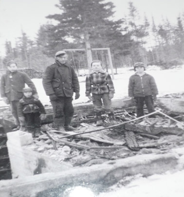 Standing in what is left of our home:  Terrence Walls with his hand on Eric Underhill's shoulder, Jim MacKenzie, Michael McLaughlin, and Dale MacKenzie.  You can see our swing tree in the back yard, and a pile of firewood by the back fence.