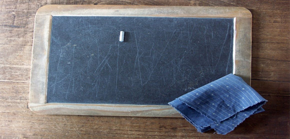 A school slate, with chalk and wiping cloth