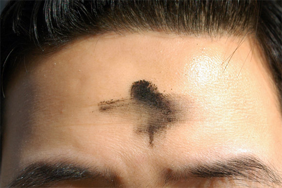 A smudged Ash Wednesday cross on the forehead