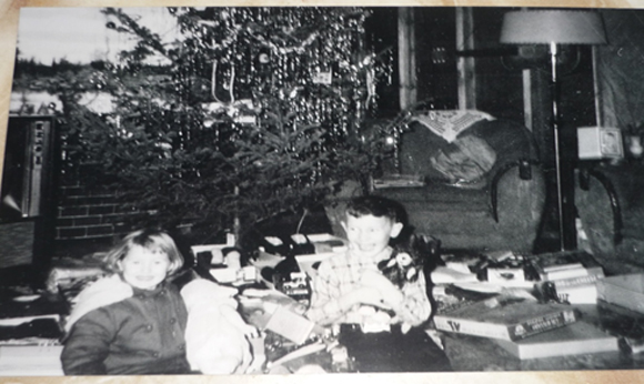 A picture of Leslie and Leonard with their Christmas presents that winter (December 1961), which shows that the house that Dad built was still unfinished.  Note the bare two-by-four studs on the living room walls.  That's just decorative brick fireplace paper taped on the wall behind the Christmas tree.