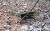 A culvert opening under the road, similar to the one we crawled through!
