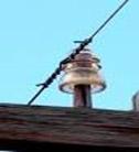 A power line insulator on a telephone pole cross beam