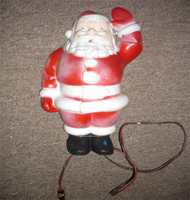 This is the actual Santa Claus ornament that Dad used to put up on top of the swing tree. The red paint on the plastic has faded over time, but it is still in good working condition.