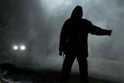 A man hitchhiking on a dark snowy night