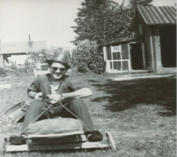 Uncle Gordon having a good laugh, sitting with his briefcase on the go-card I made.   In the background is the shed that Dad built, with the attached play house