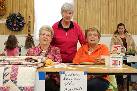 Margaret Mountain, Carrie Weaver and Lillian Brennan of the Blackville Women's Institute selling tickets on quilts